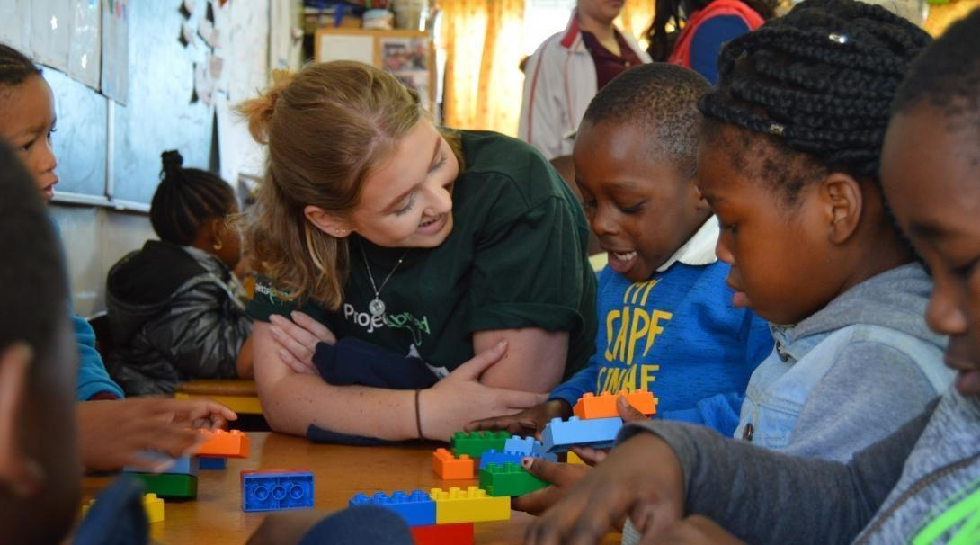Volunteer in South Africa sits with children during a lesson